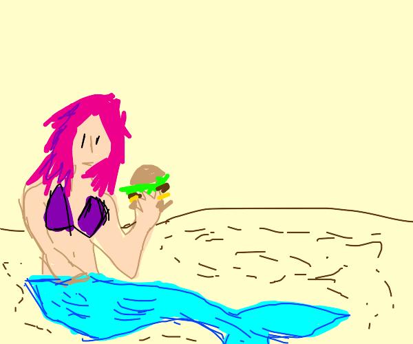 mermaid on sand holding a burger