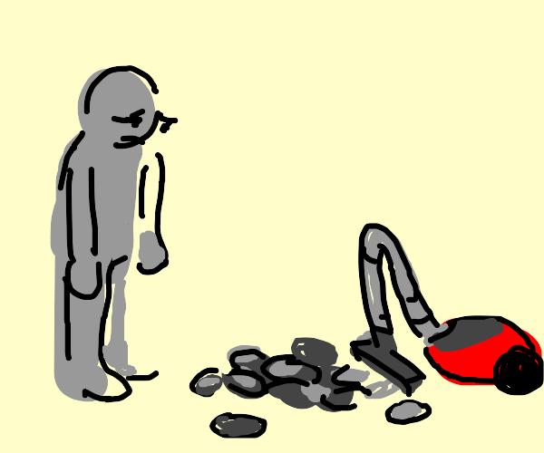 a vacuum is vacuuming rocks, man is saddened
