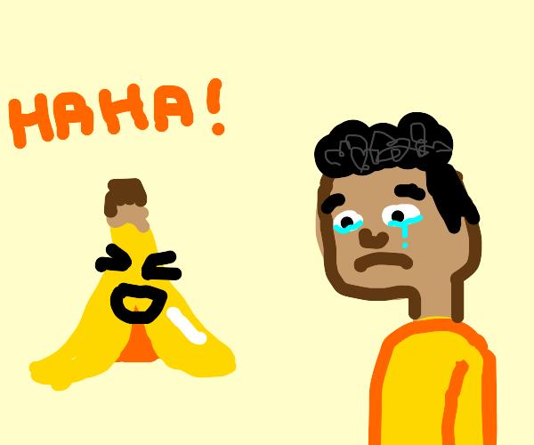 A sad man gets laughed at by the banana peel