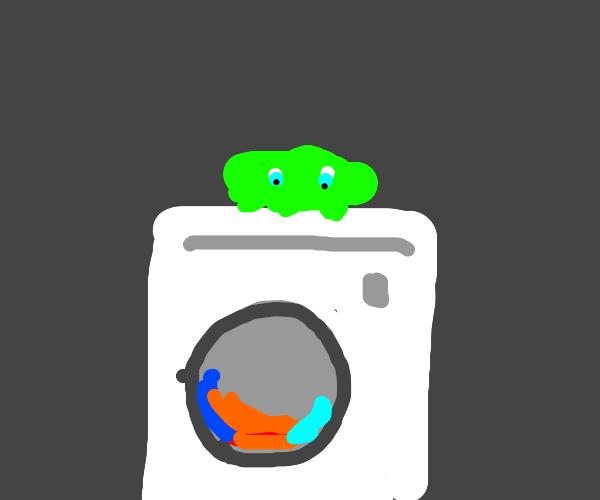 Orange blob with eyes on washing machine
