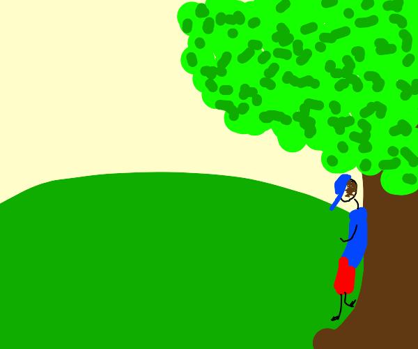 guy standing under big tree