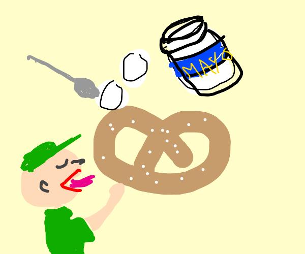 A guy enjoying his mayo-covered pretzel