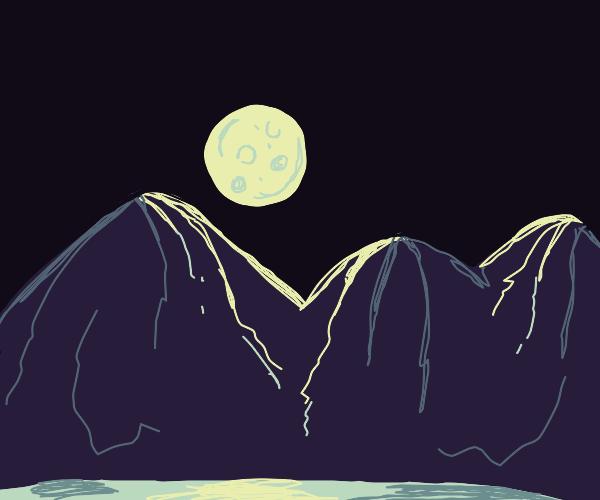 Full moon rises over mountain range with lake