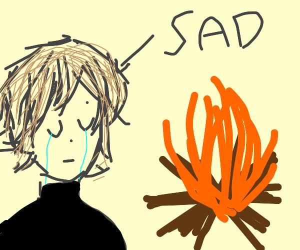 Sad boy wearing black watches campfire