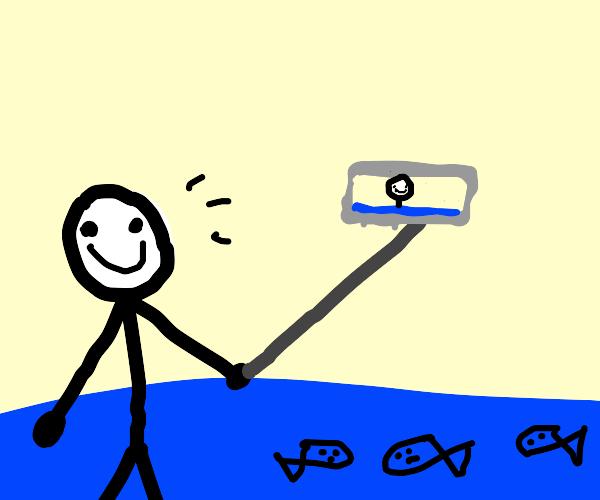 man filming with selfie stick in ocean