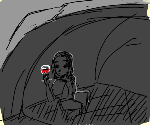 Girl drinks wine in cave