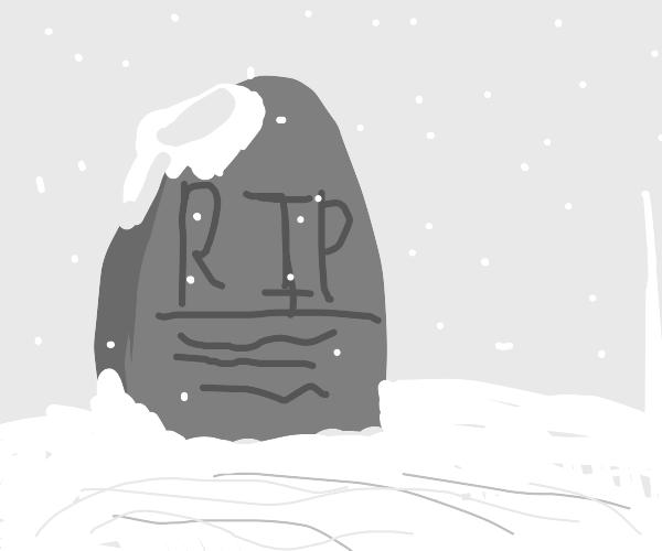 A small grave stone in a snowy winter scene