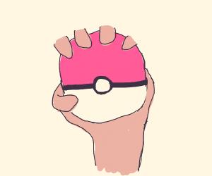 a hand holding a pokeball