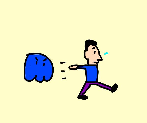 A man running away from a blue ghost