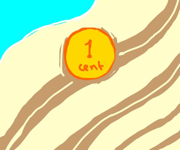 1 cent coin lying on the beach