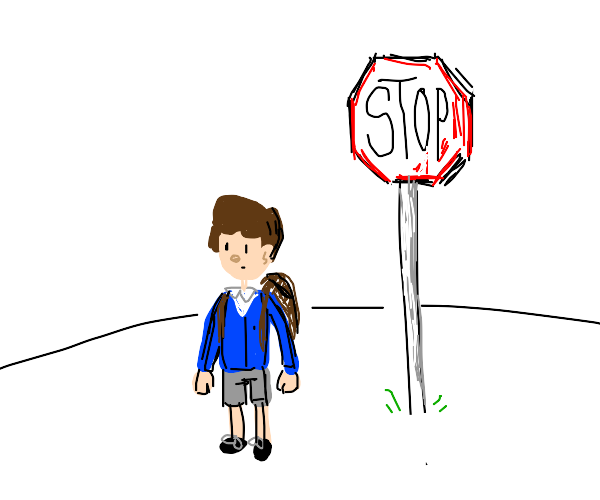 school boy next to stop sign