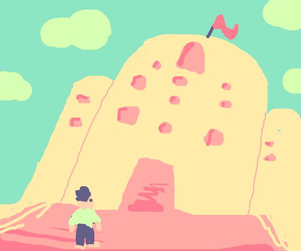 Man stands outside gigantic sandcastle