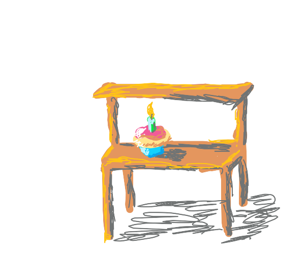 A smiling cupcake on a desk with a candle