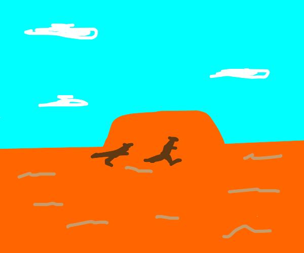 Kangaroos jumping in front of Uluru