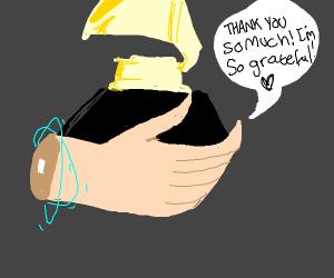 a hand holding a grammy