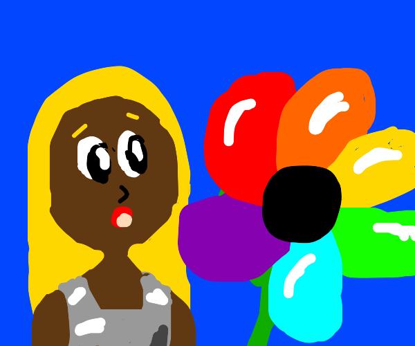 Blonde girl amazed by rainbow flower.