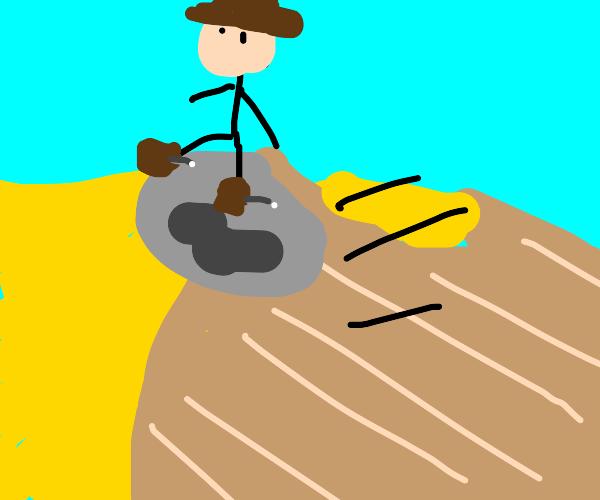 A cowboy riding a rock in the desert
