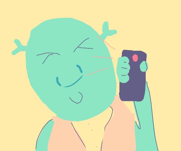 Shrek is taking a selfie.