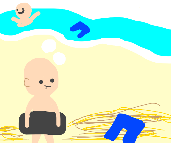 Naked man looking at his pants at the beach