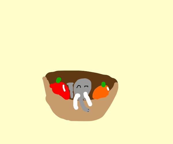 Tiny elephant chillin in a fruit basket