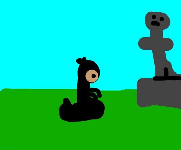 Ninja kneels in front of statue
