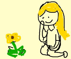 girl looks at flower