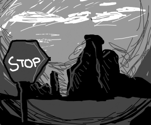 A stop sign in front of the ruins of a city