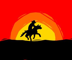 Cowboy riding into sunset