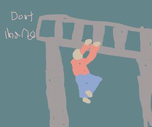 Man hanging from bridge