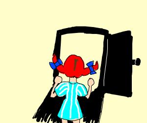 Little redhaired girl looking through door