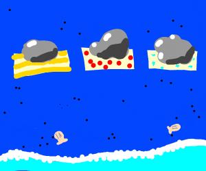Three rocks, sitting on a blue beach.