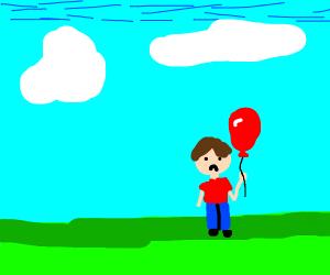 Boy holding a balloon is sad