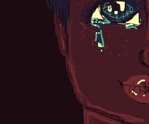 Tear falls from emerald eye in the dark