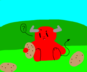 red devil sits on grass with poatos
