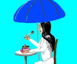 eating cake under a umbrellla