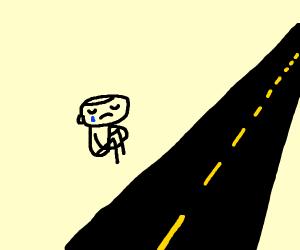 sad man sits by empty road
