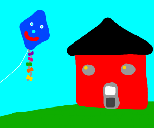 a kite with a face next to red house