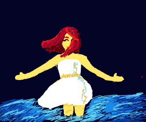 red haired woman walks through the ocean