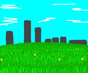 Grassy field overlooking some buildings