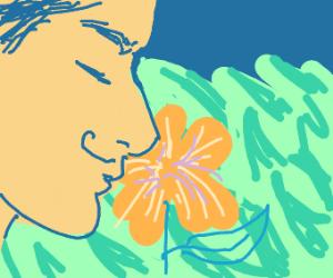 Man smelling orange flower in a field