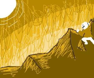 man climbs mountain to a sunset
