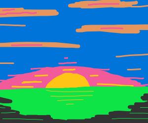 A sunrise on a blue sky over the green grass