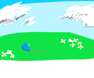 a blue balloon with red string in a field