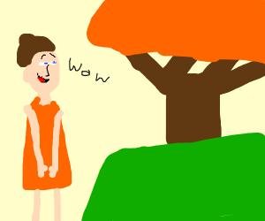 Girl with orange dress suprised at tree