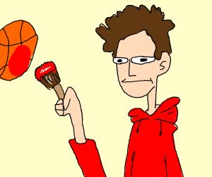 Man in red hoodie paints a basket
