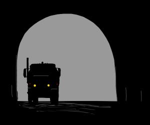 A truck driving through a dark tunnel