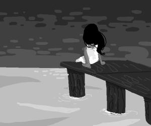 Girl sitting on dock overlooking water