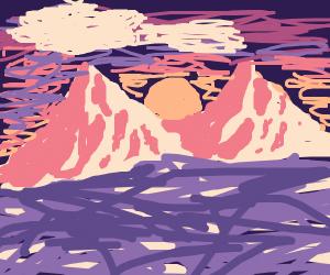sun sets behind mountainrange