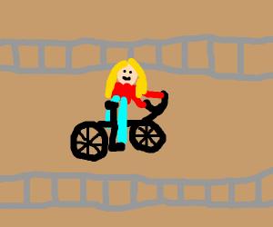 woman on bike rides across train tracks