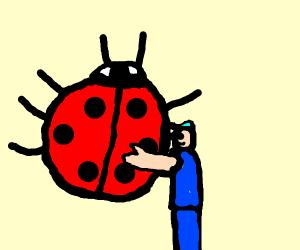 Guy is hugging a giant ladybug. Very sweet